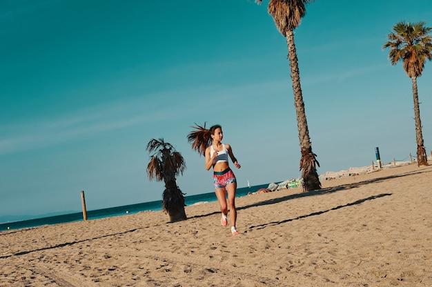 勝つことを決意した。屋外で運動しながらジョギングスポーツ服の美しい若い女性の全長