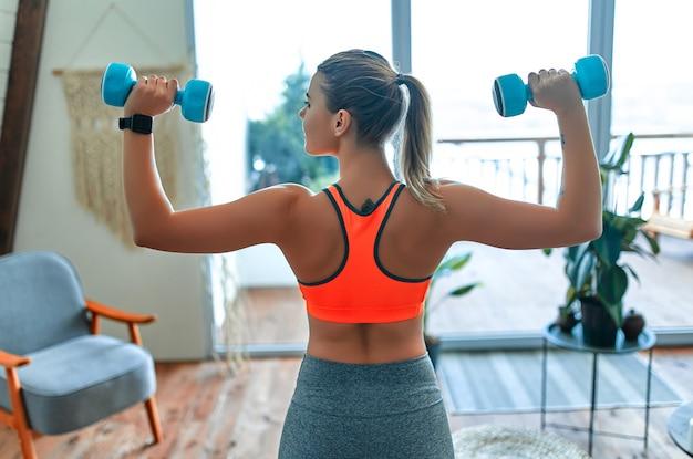 自宅で体重を減らし、ダンベルで運動していると決心した女性。スポーツとレクリエーションのコンセプト。彼女の手に青いダンベルを持つスポーツウェアの美しい女性。