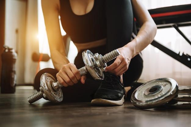 自宅で体重を減らし、ダンベルで運動していると決心した女性。スポーツとレクリエーションのコンセプト。スポーツウェアの美しい女性