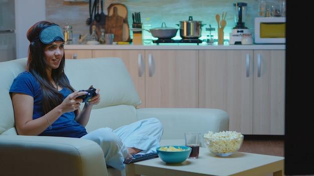 밤에 거실에서 비디오 게임을 하는 결정적인 여성. 흥분한 게이머 여성은 소파에 앉아 콘솔과 무선 컨트롤러를 사용하여 비디오 게임을 하고 승리합니다.