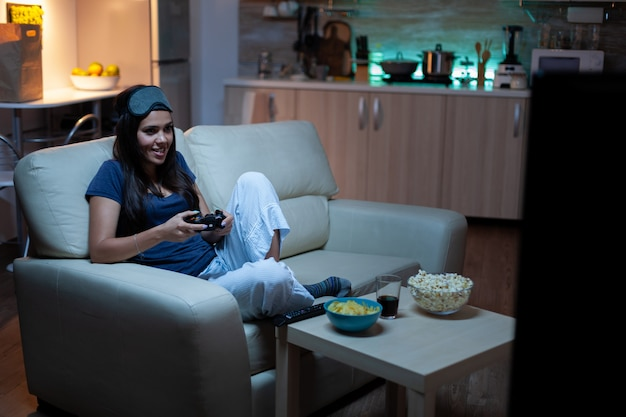 Determined woman playing video game in living room at night