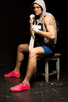 Determined young boxer sitting on a stool waiting for his fight