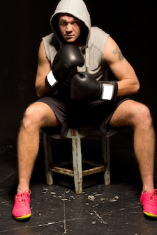 Determined young boxer sitting on a wooden stool