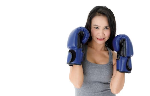 戦いの姿勢で立って、白い背景に笑顔でカメラを見て青いボクシンググローブで若いフィットアジアの女性を決定しました