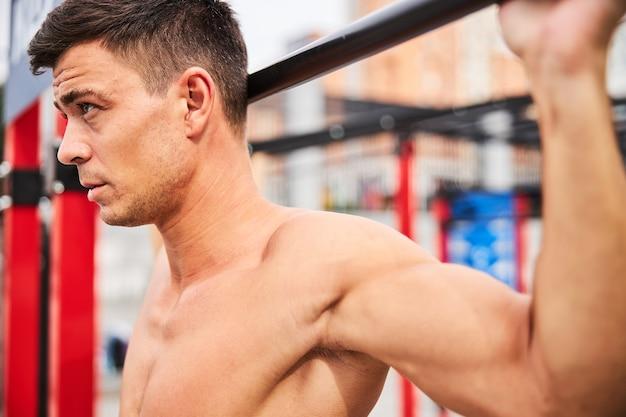 決心した若い筋肉質の男性が野外でスポーツグラウンドの鉄棒で懸垂をしている