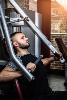 ジムでフィットネスマシンに取り組んでいる断固とした若い筋肉男