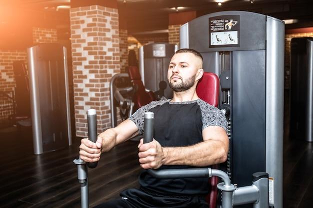 체육관에서 피트니스 기계에서 작업하는 젊은 근육 남자를 결정