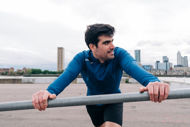 Determined young spanish man stretching for workout