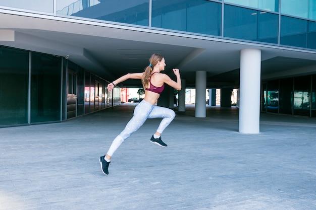 Решительная молодая женщина бежит за пределы здания