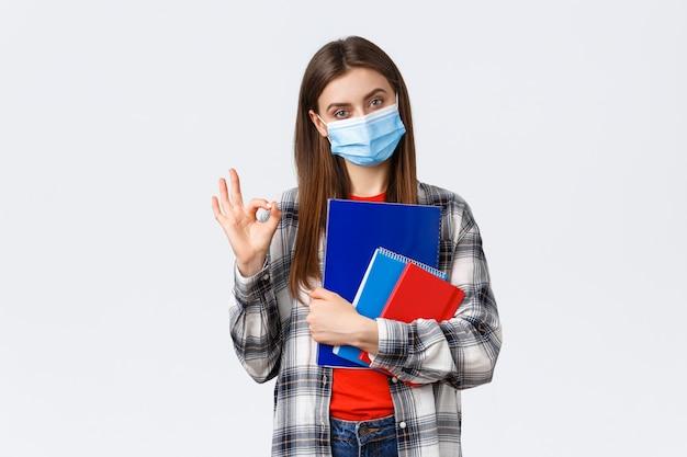 Решительная молодая женщина, студентка в медицинской маске с тетрадями и учебным материалом, показывает, хорошо, без проблем