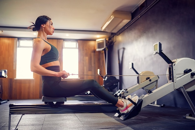 Решительная молодая женщина, тренирующаяся на тренажере в фитнес-студии