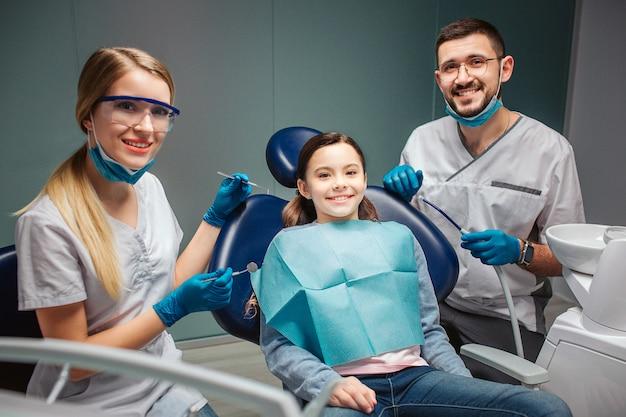陽気な素敵な若い男性女性detists座るし、歯科用椅子に子供とポーズ