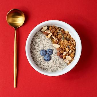 デトックスと健康的なスーパーフードの朝食ボウルのコンセプト。ビーガンココナッツミルクチアシードプディング、ブルーベリー、ナッツ。オーバーヘッド、トップビュー、フラットレイアウト。