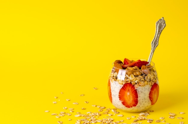 Detox chia pudding with strawberries, oatmeals and nuts in a glass on  yellow  front view copy space