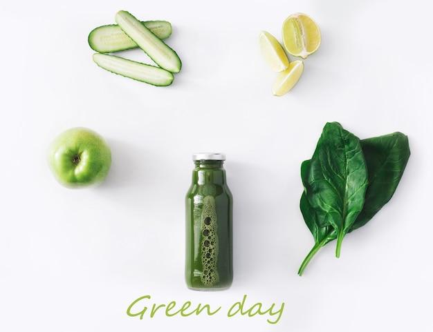 デトックスクレンズドリンクコンセプト、緑の野菜のスムージーの成分。減量ダイエットや空腹時のボトルに入った自然で有機的な健康ジュース。白で隔離されるキュウリ、リンゴ、ライム、ほうれん草のミックス