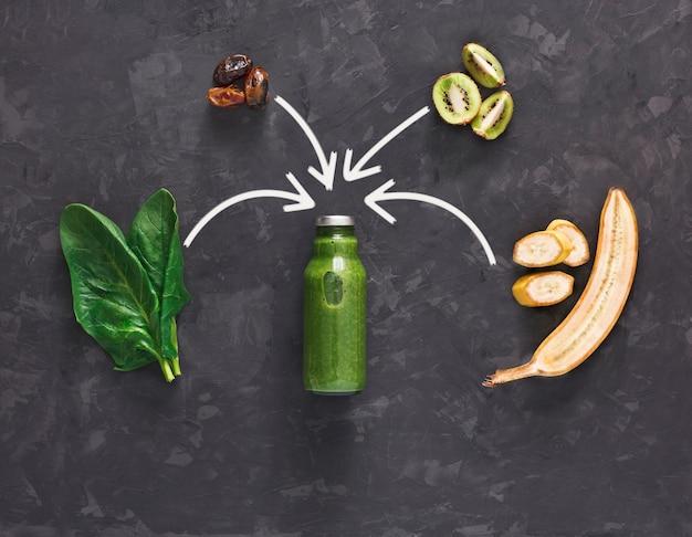 デトックスクレンズドリンクコンセプト、緑の野菜のスムージーの成分。減量ダイエットや空腹時のボトルに入った自然で有機的な健康ジュース。キウイ、バナナ、ほうれん草のミックス、フラットブラック