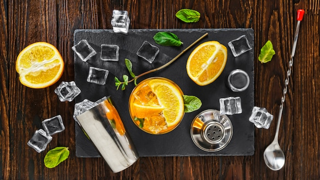 Detox cocktail with orange cooked in a shaker with ice. refreshment. gluten free drink