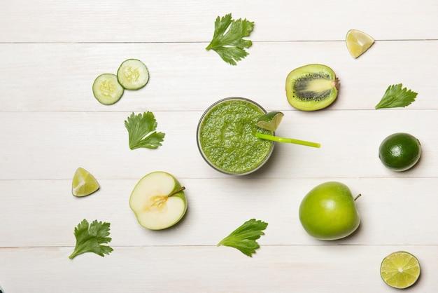 Концепция детокса. стеклянная банка свежего напитка зеленый смузи, листья шпината, огурец, яблоко, плоды лайма.