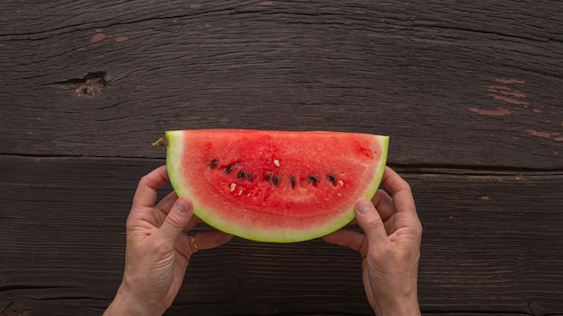 Detox concept. slices delicious ripe watermelon in woman's hands on wooden background