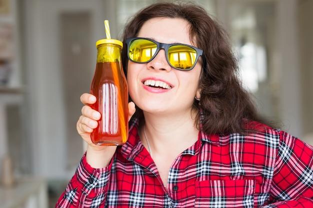 デトックス、ダイエット、健康的なライフスタイルのコンセプト。女性はチェリージュースを見せています。