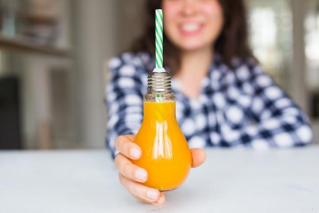 デトックスダイエットと健康的なライフスタイルのコンセプトの女性はオレンジジュースを示しています