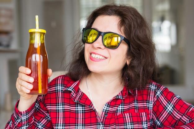 해독, 다이어트 및 건강한 라이프 스타일 개념-젊은 여자는 신선한 주스 한 병을 보유하고 있습니다.
