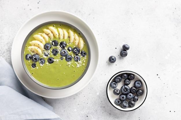 Detox green smoothie in dark bowl vegan breakfast with superfood green powder banana blueberry