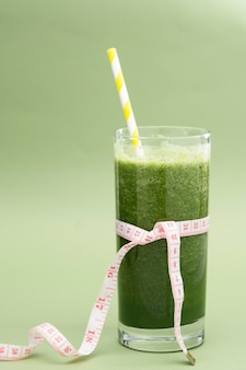 Detox green smoothie glass for loose weigh, dieting, green background. healthy food.