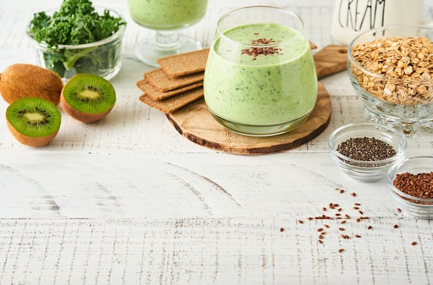 Detox green smoothie with kale, spinach and kiwi on a light gray slate