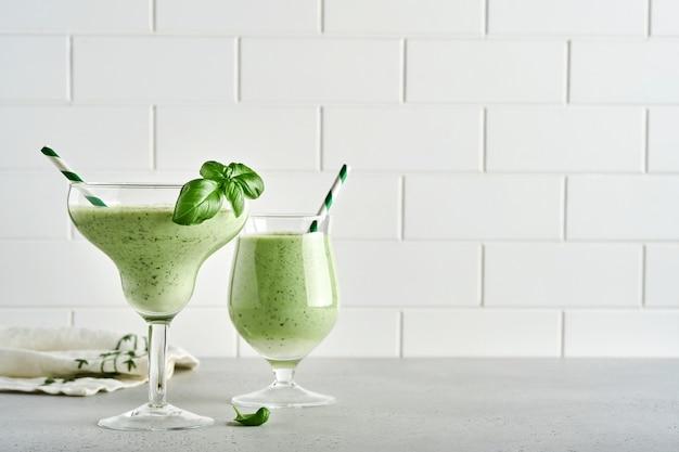 밝은 회색 슬레이트, 돌 또는 콘크리트 배경에 칵테일 잔에 신선한 바질 잎으로 장식된 해독 녹색 야채 주스 또는 스무디. 복사 공간이 있는 상위 뷰입니다.