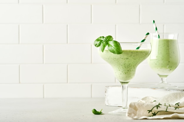 ライトグレーのスレート、石、またはコンクリートの背景にカクテルグラスに新鮮なバジルの葉を添えたデトックスグリーン野菜ジュースまたはスムージー。コピースペースのある上面図。
