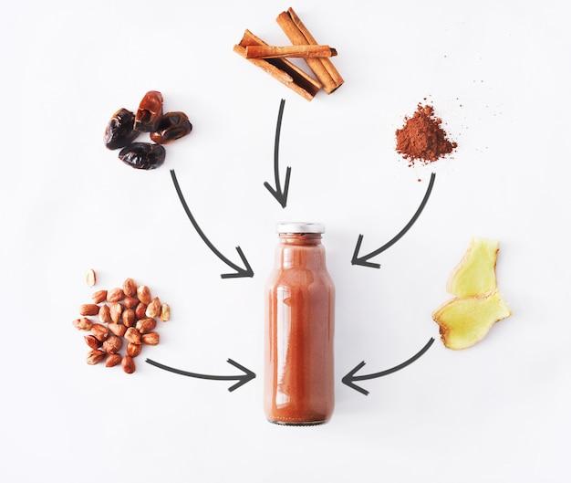 デトックス健康ドリンクコンセプト、チョコレートのスムージーの成分。減量ダイエットや空腹時のボトルに入った天然の有機ジュース。ココアパウダー、生姜、日付フルーツ、シナモンミックス白で隔離
