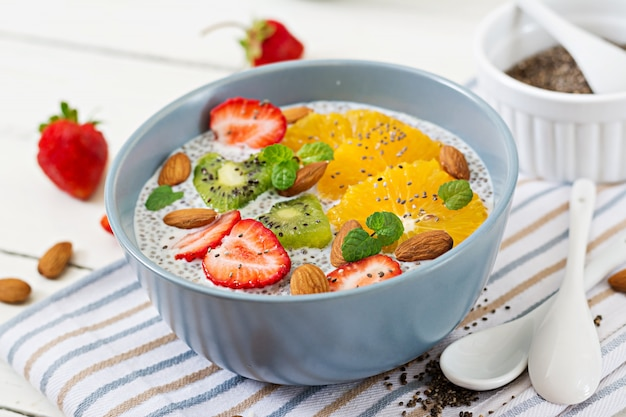 Detox and healthy superfoods breakfast in bowl. vegan almond milk chia seeds pudding with strawberries, orange and  kiwi.