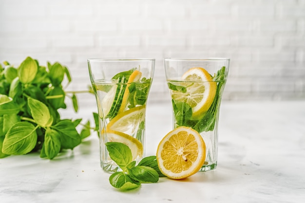 Detox infused water with cucumber and lemon on white background