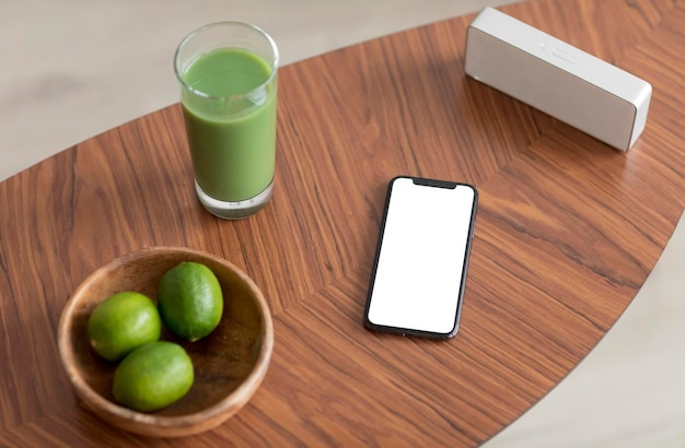 Succo di disintossicazione e smartphone con schermo vuoto su un tavolo di legno