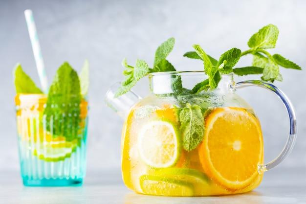 Детокс-лимонадный напиток из воды, лимона, апельсина и листьев мяты в прозрачном чайнике. чайный коктейль из лайма и мяты со льдом. летний свежий напиток. копировать пространство