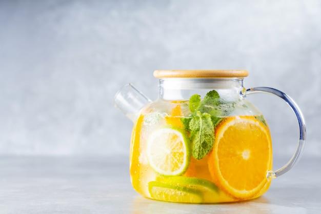 Детокс-лимонадный напиток из воды, лимона, апельсина и листьев мяты в прозрачном чайнике.