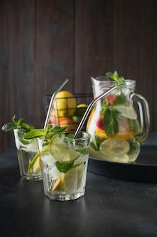 Detox lemonade with lime, orange, lemon, strawberry in glass and jar.