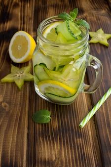 Детокс или настоянная вода с огурцом, карамболой и лимоном на коричневом деревянном фоне