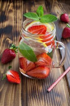 음료수 잔에 딸기와 레몬을 넣은 해독 또는 주입 된 물