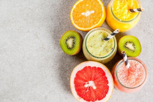 デトックスオーガニックダイエットドリンク、自家製トロピカルスムージーキウイ、オレンジ、グレープフルーツ、ポーションジャー、食材、灰色の石のテーブルの上。上面図