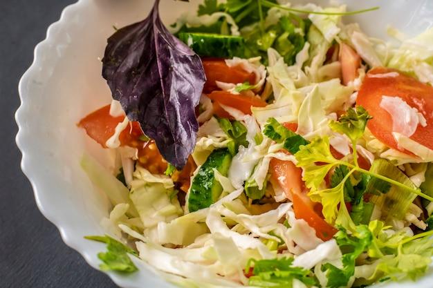 Детокс-сальсад в белой керамической миске с изолированными капустой, томазо и базиликом