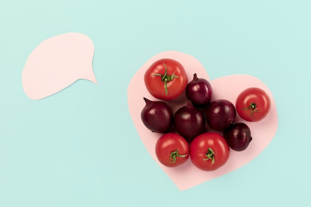 Detox super food selection from fresh vegetables in paper heart on blue background. healthy food nutrition. conceptual composition with copyspace
