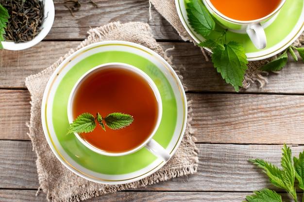 Detox tea of fresh nettles on the wooden table