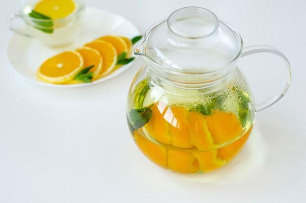 オレンジ色の果物とミントと黄色い水仙の花と透明のティーポットのデトックス茶