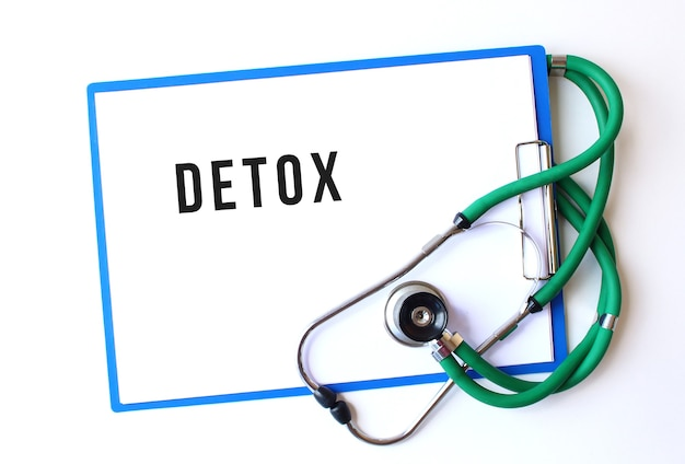 Detox text on medical folder with documents and stethoscope on white surface