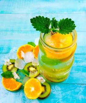 デトックスウォーターカクテル。アイスキウイと青い木製テーブルの上のオレンジの健康ドリンク