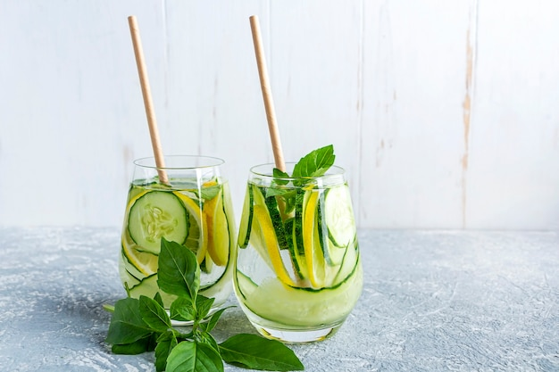 Детокс-водный напиток с огурцом и лимоном на светло-сером столе и белом фоне стены