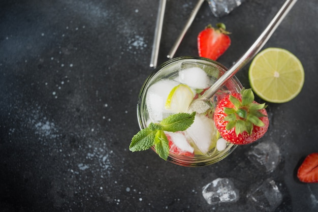 Detox water or mojito with lime, strawberry in glass