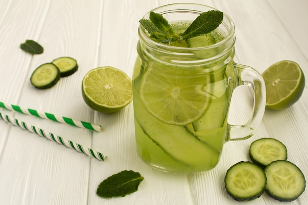 Detox water  with cucumber and lime on the white wooden background